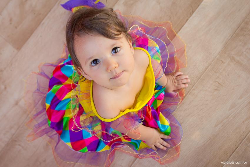 menina vestida de palhaço com vestido colorido