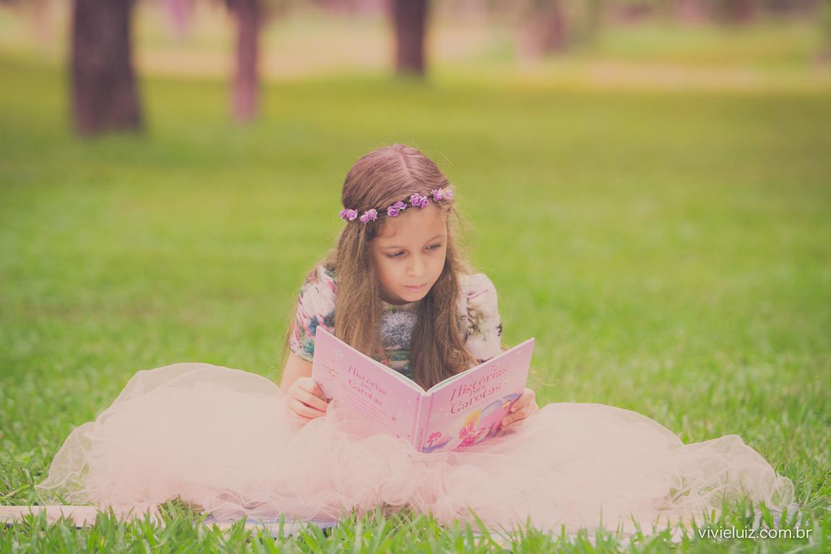 menina lendo livro no campo verde