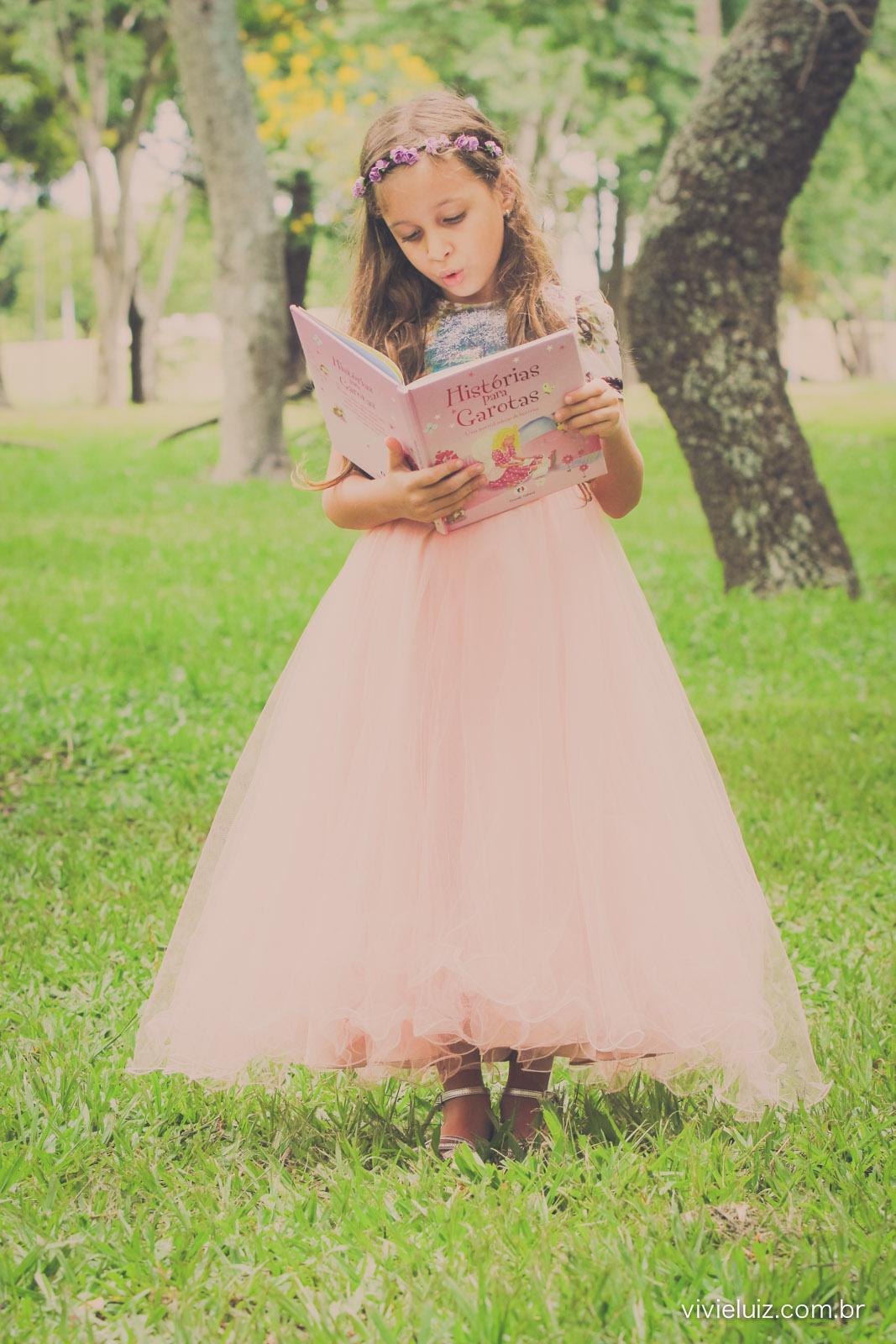 menina com vestido rosa lendo livro em parque verde