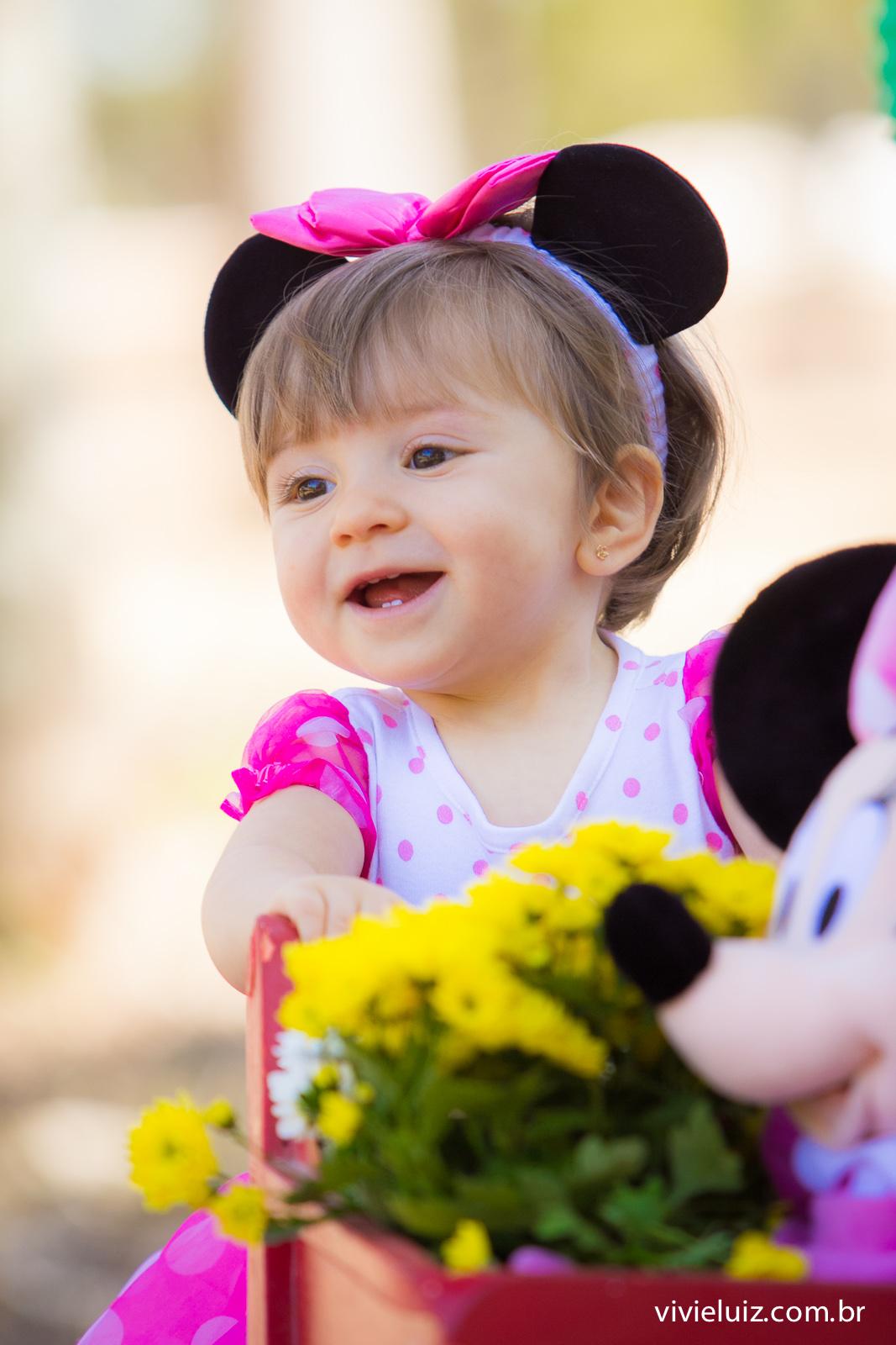 menina empurrando carrinho de compras com minie e flores amarelas