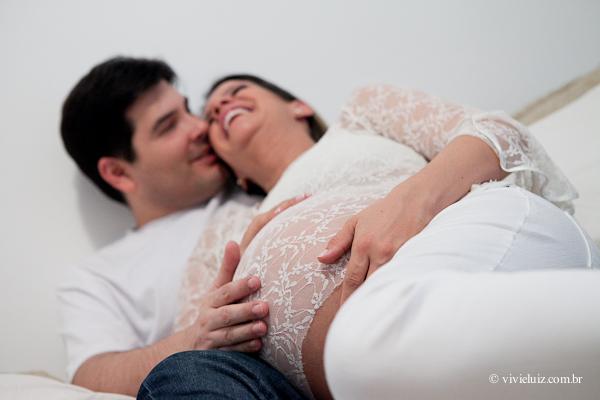 Casal deitado com mão na barriga da mãe grávida