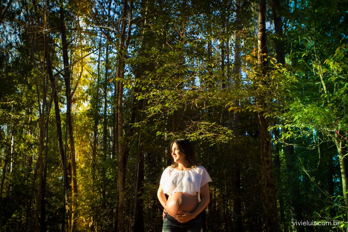 Gestante em floresta com luz de pôr-do-sol