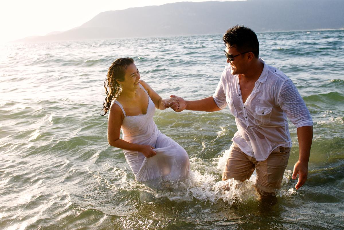 Noivo ajuda noiva a sair do mar