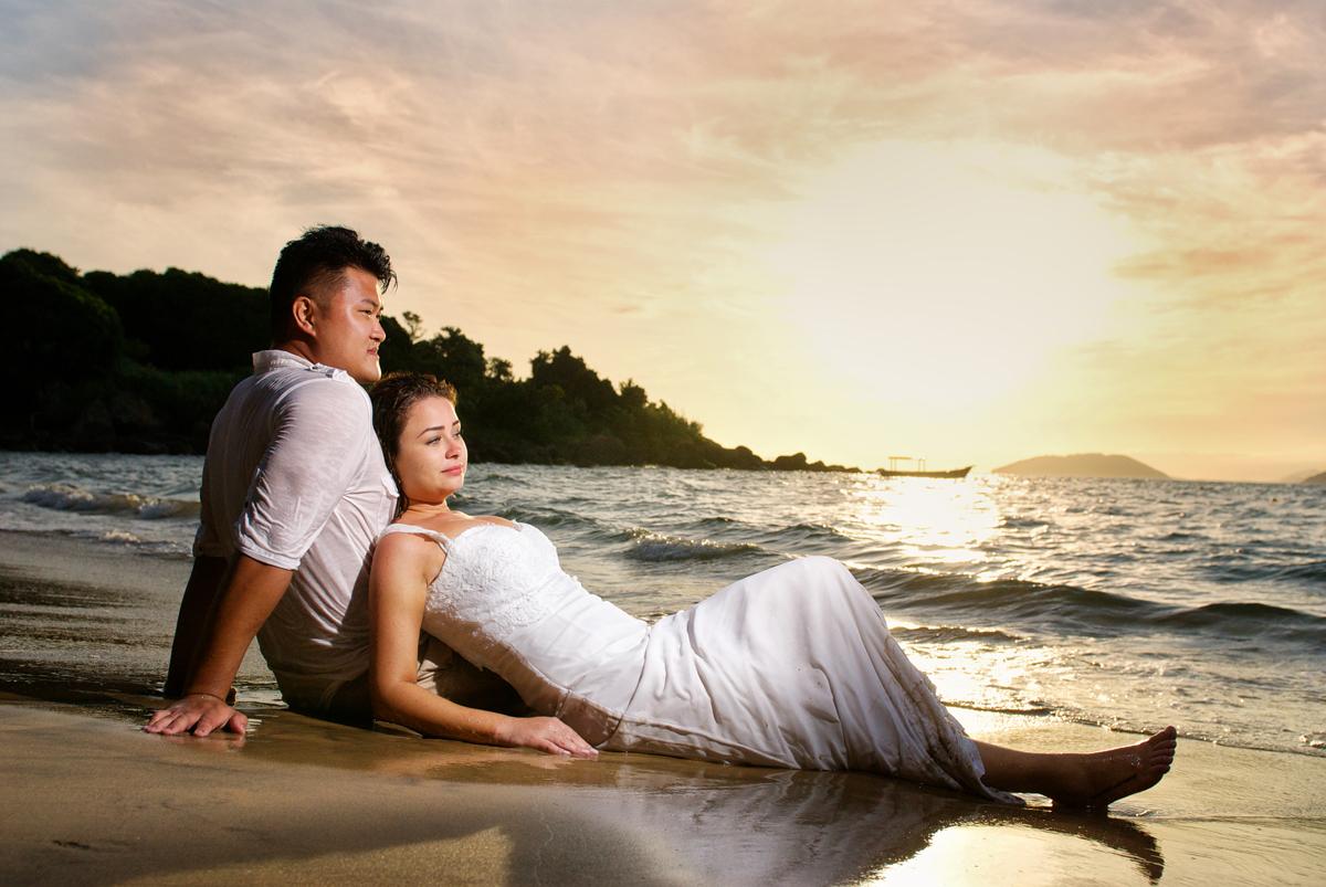 noivos descansam na praia ao por do sol