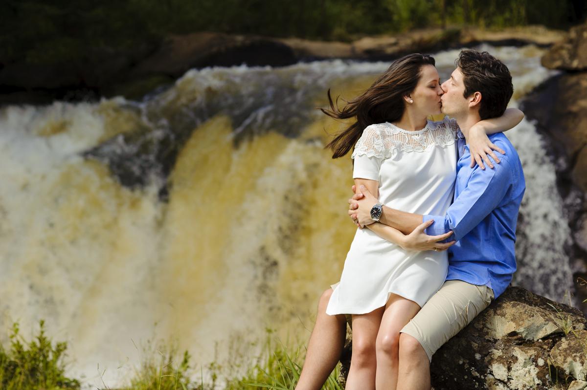 noivos se beijam frente a cachoeira