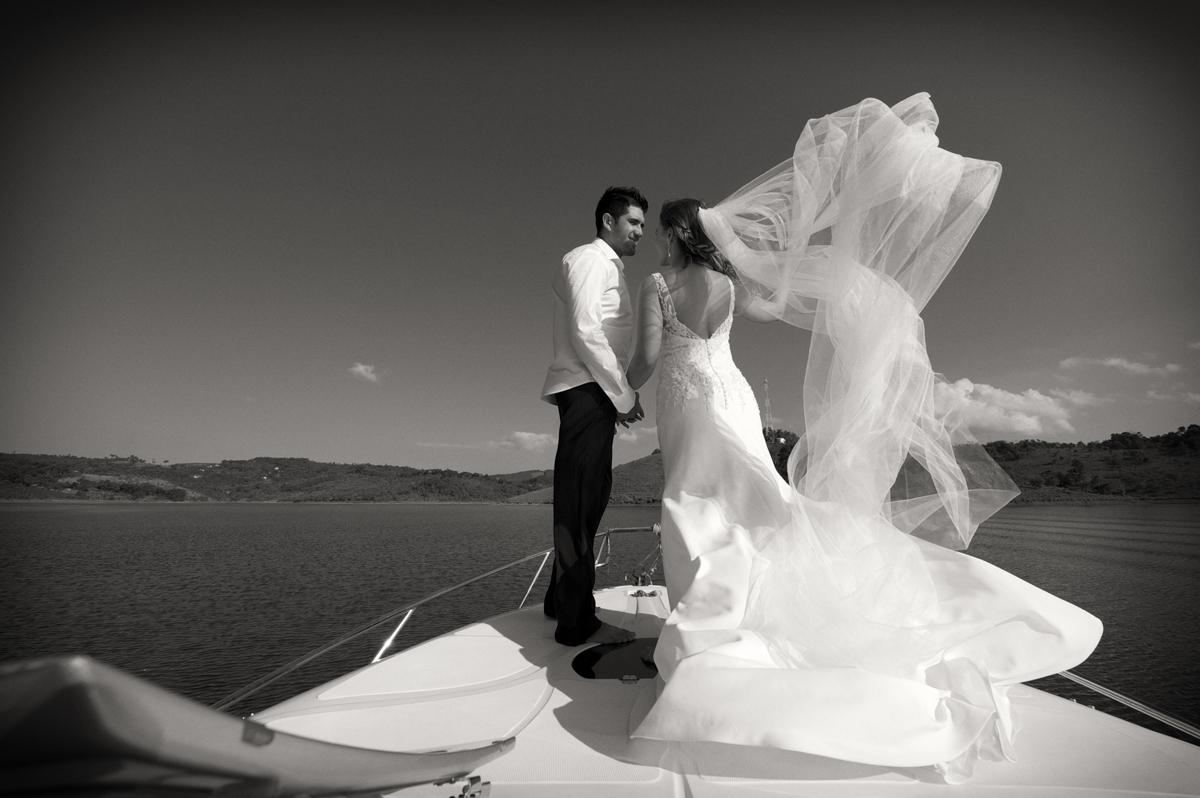 Casal de noivos se beijam na proa da lancha