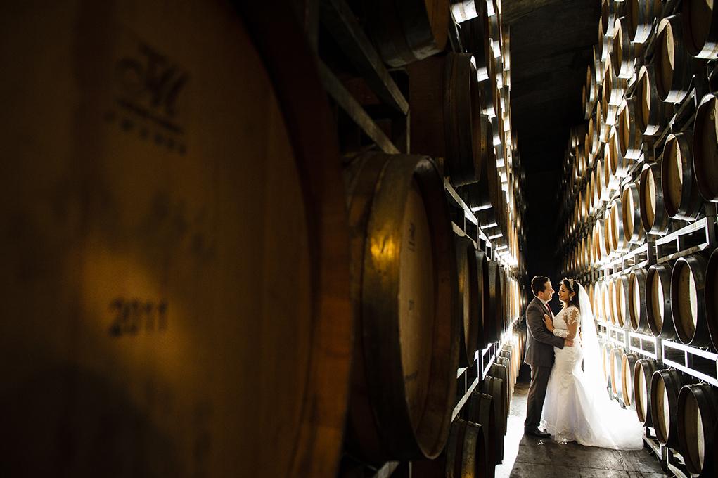 noivos se beijam na adega de vinhos