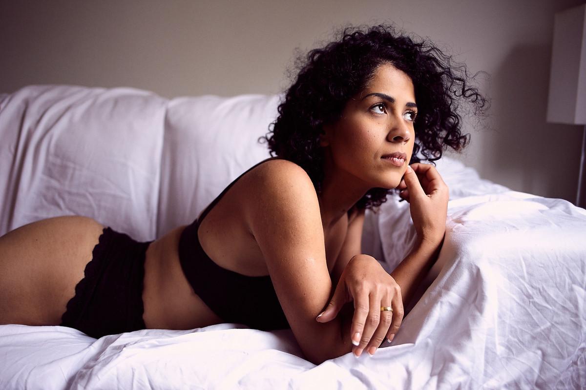 Deitada sobre o sofá, usando lingerie preta, Adriely olha serenamente em direção à luz, com seus cabelos movimentados pelo vento, em foto de Jon K. Roz, retratista especializado em ensaios femininos
