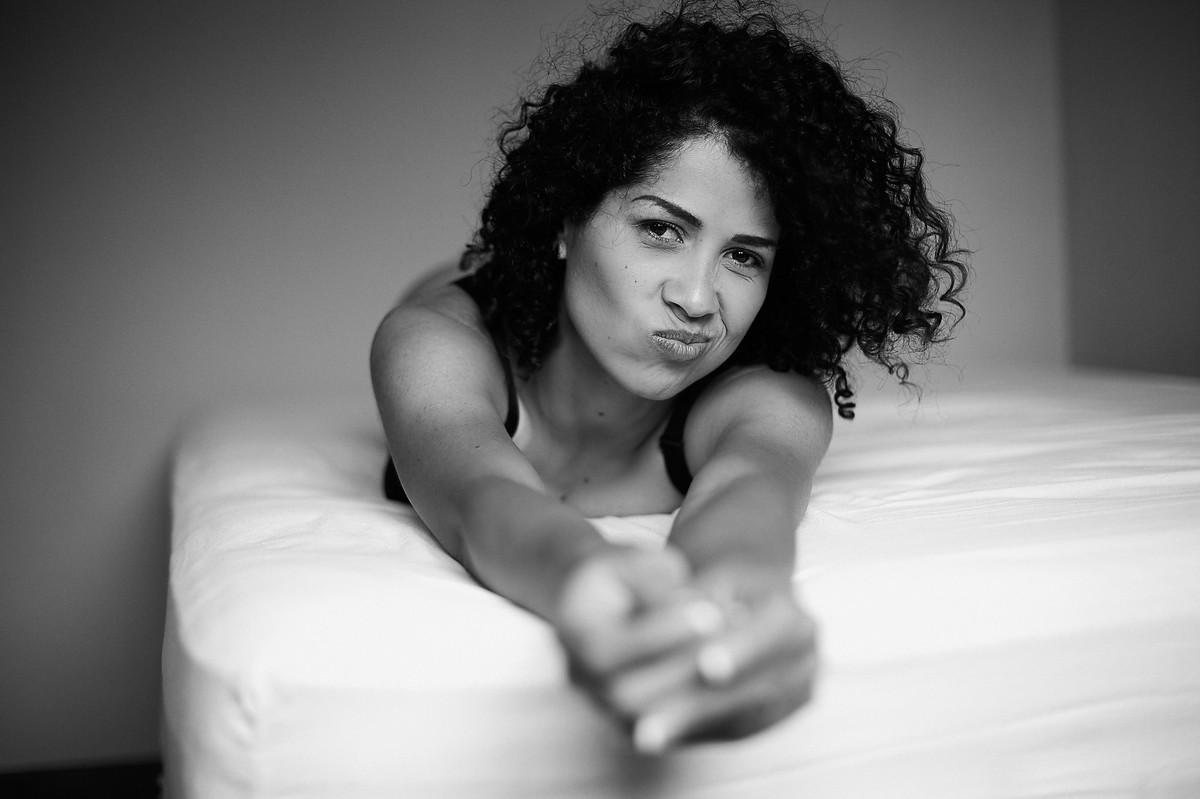 Charme, ao fazer careta, da linda Adriely, deitada sobre a cama, com os braços estendidos em direção à câmera, em click preto e branco do fotógrafo Jon K. Roz, que faz retratos femininos em Curitiba