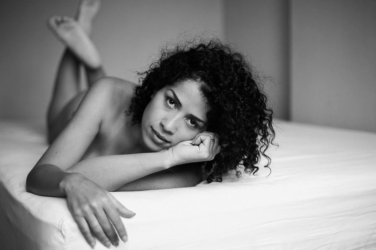 Click, em preto e branco, do fotógrafo Jon K. Roz, de retratos intimistas femininos, com a bela Adriely, sobre a cama, deitada, com o corpo inclinado para a direita, olhando diretamente