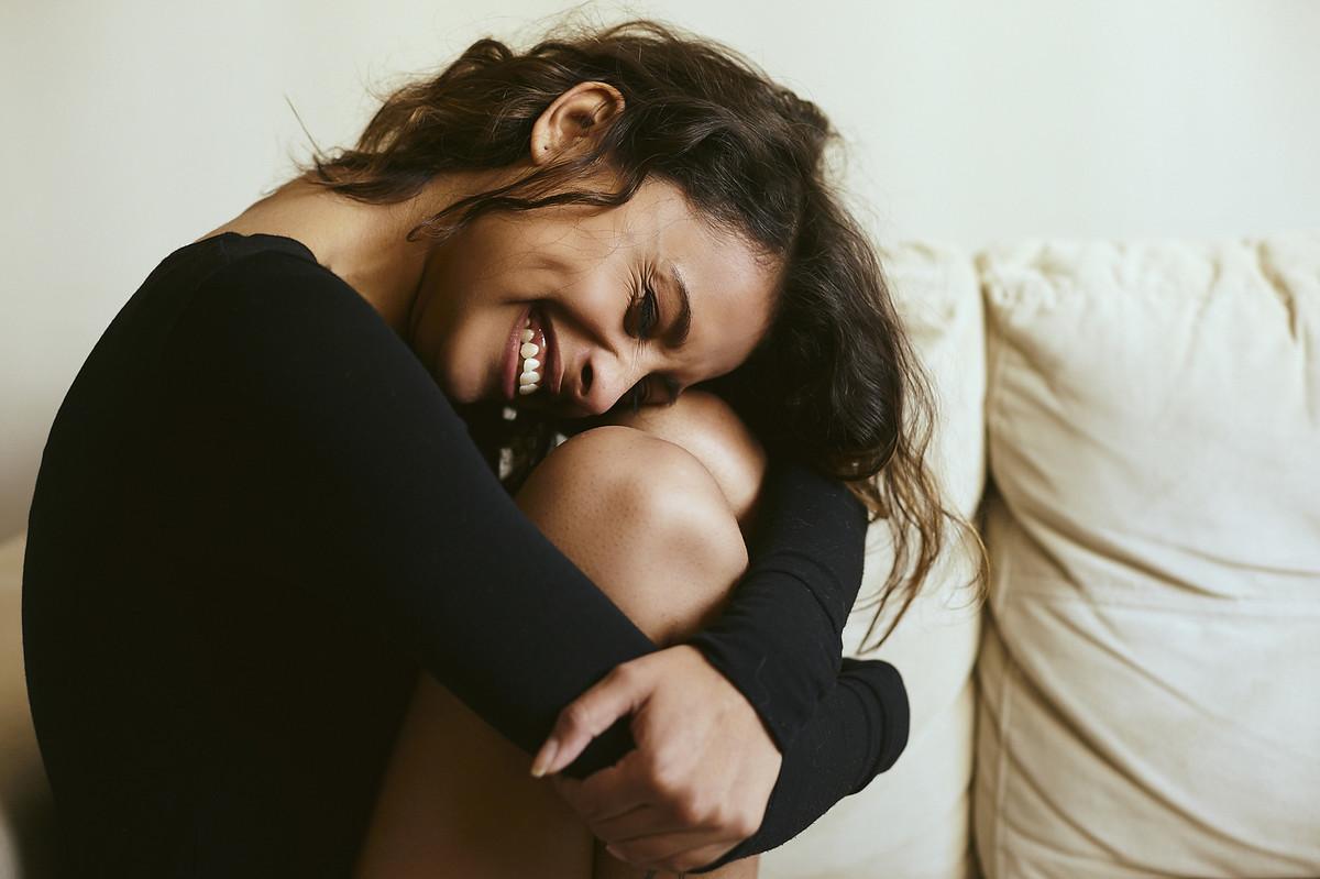A linda Andry, sorrindo sentada no sofá, abraçando as próprias pernas, em ensaio boudoir do fotógrafo Jon K. Roz, especializado em retratos femininos