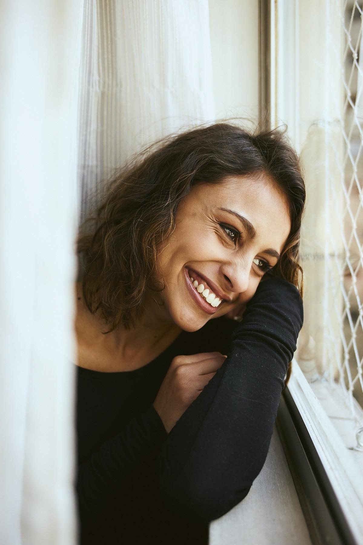 Sorriso da Andry, contra a janela e levemente ocultada por uma cortina, em click do fotógrafo Jon K. Roz