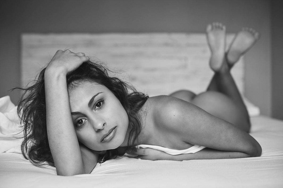 Nu artístico, em preto e branco, de ensaio boudoir do fotógrafo Jon K. Roz, retratando a linda Andry, sobre a cama, com olhar sereno e direto
