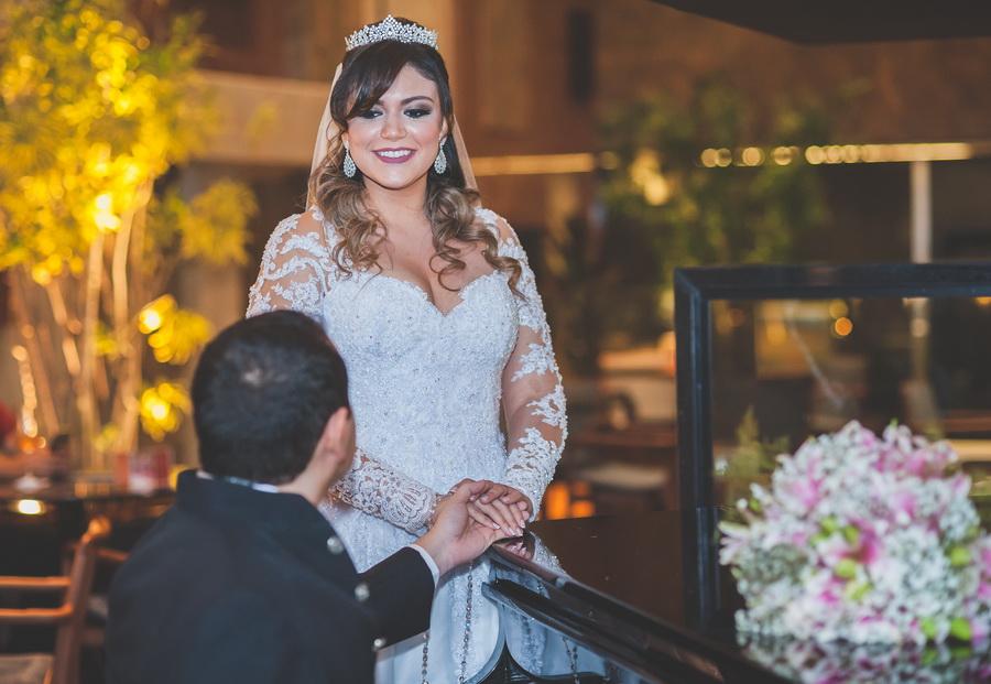 noivo ajoelhado segurando a mão da noiva num lindo momento registrado pelo FOTOGRAFO DE CASAMENTO FORTALEZA CE JULIO LUCENA no salão do Gran Marquise Hotel
