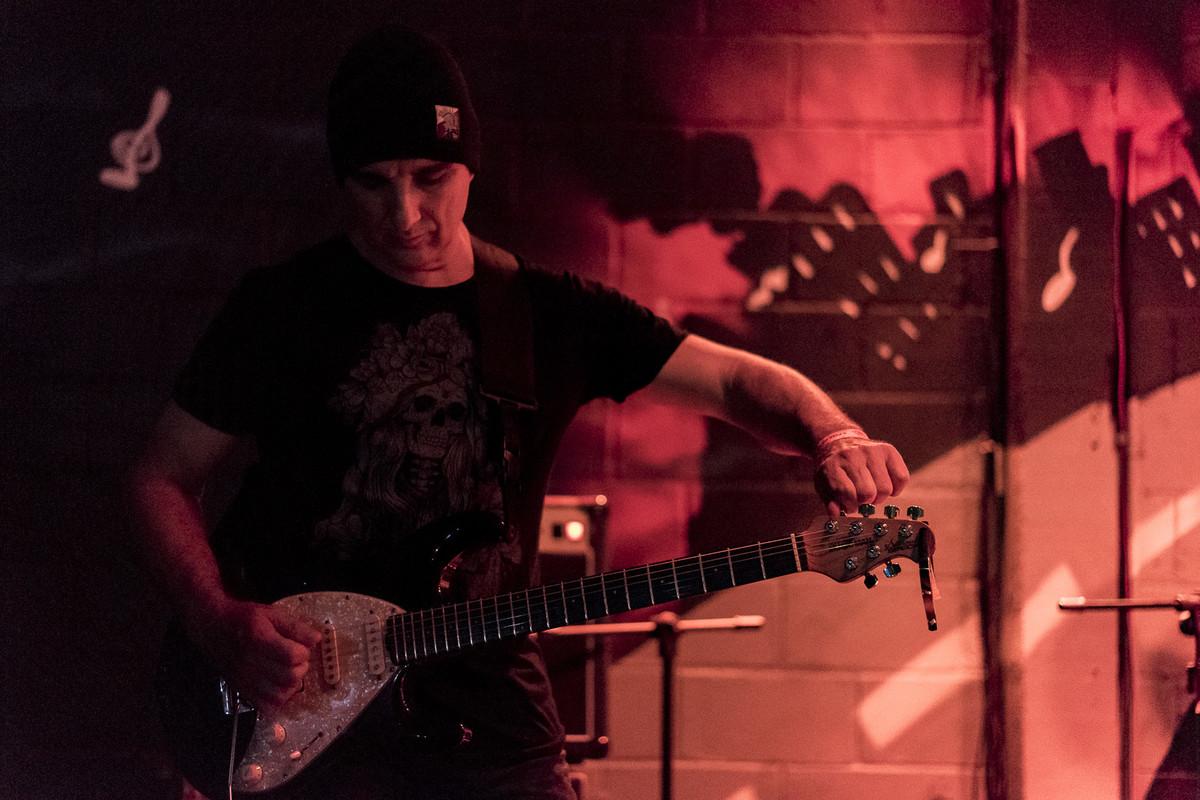 Nilo Nunes do Uns e Outros afinando a guitarra Music Man Silhuette Special Marcos Bilate