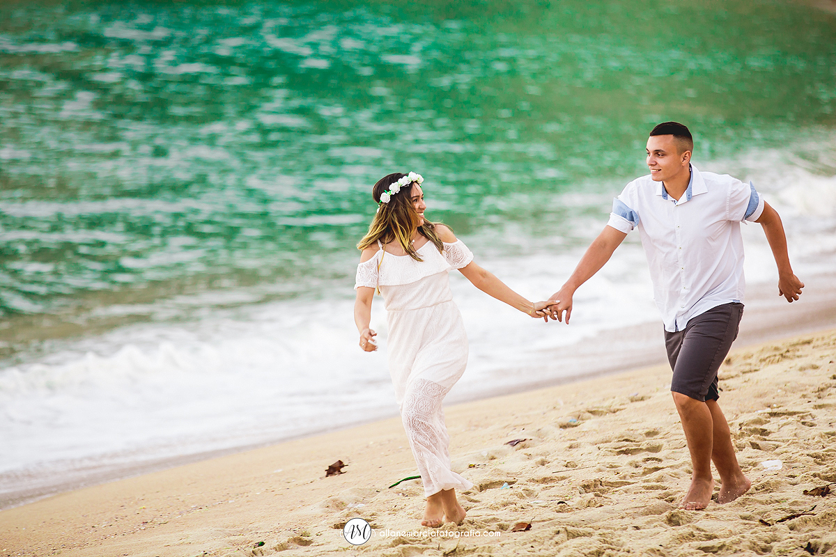 noivos correndo na praia de mãos dadas