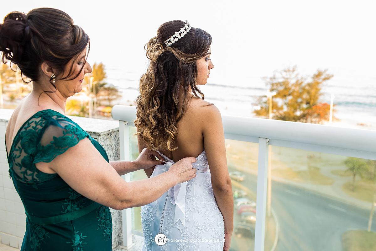 mãe da noiva prendendo vestido