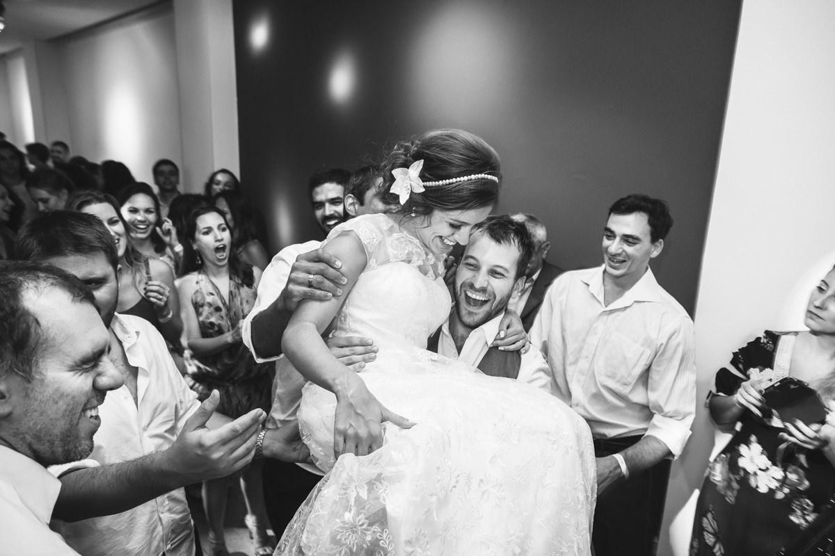Noivo Pedro pegando no colo a noiva Karine na festa de casamento na Galeria Scenarium/Rio Scenarium, Rio de Janeiro/RJ