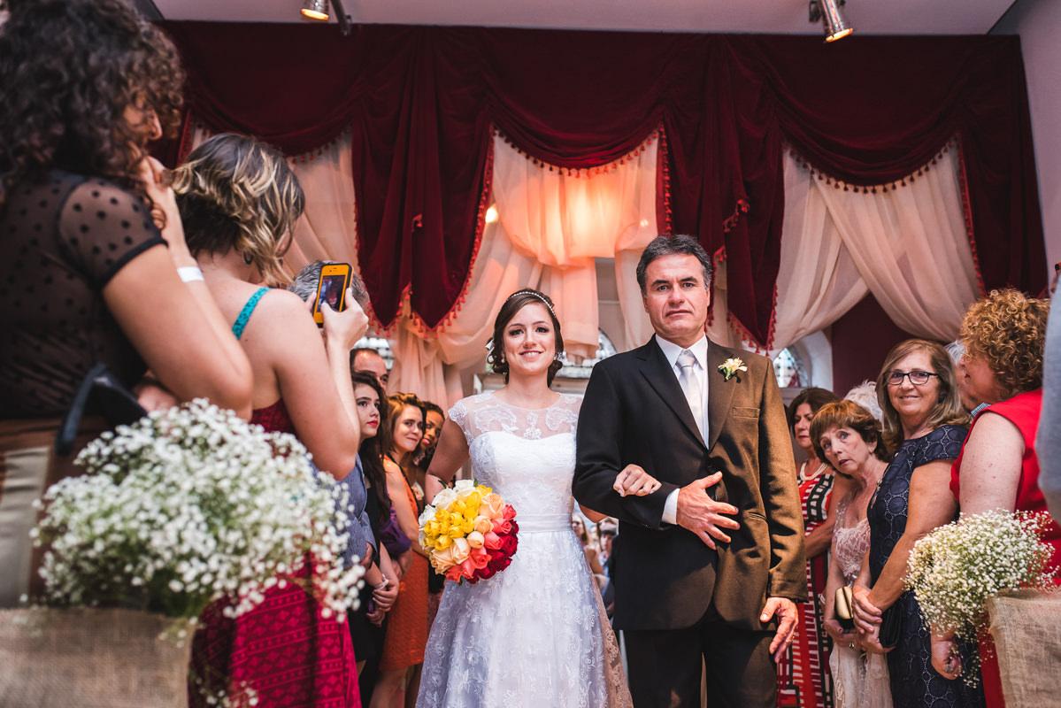 A entrada da noiva Karine com seu pai na cerimônia do seu casamento na Galeria Scenarium/Rio Scenarium, Rio de Janeiro/RJ