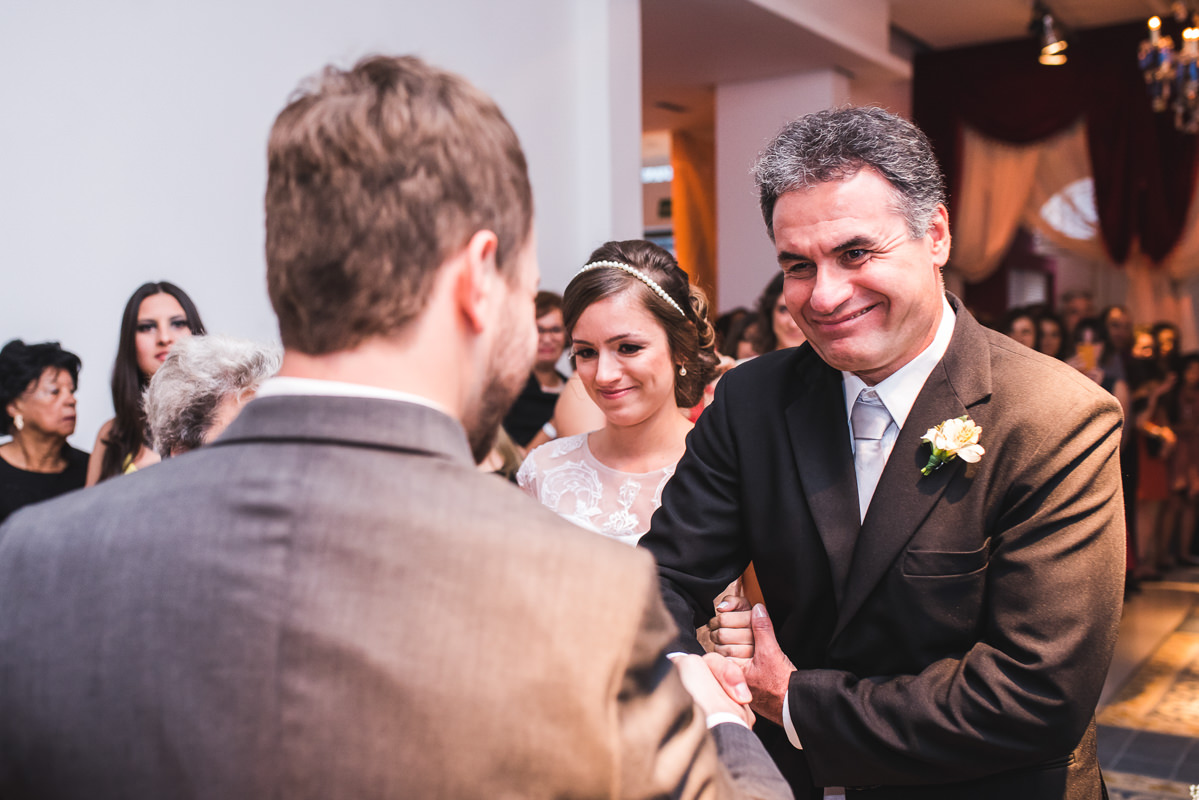 O pai da noiva levando sua filha Karine até o noivo Pedro na cerimônia do casamento na Galeria Scenarium/Rio Scenarium, Rio de Janeiro/RJ