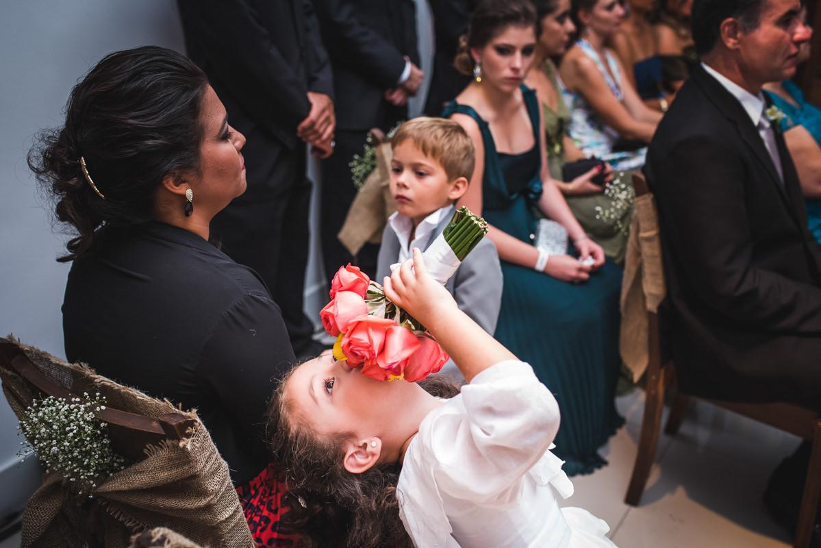 A daminha brincando com o buquê da noiva na cerimônia do casamento de Karine e Pedro na Galeria Scenarium/Rio Scenarium, Rio de Janeiro/RJ