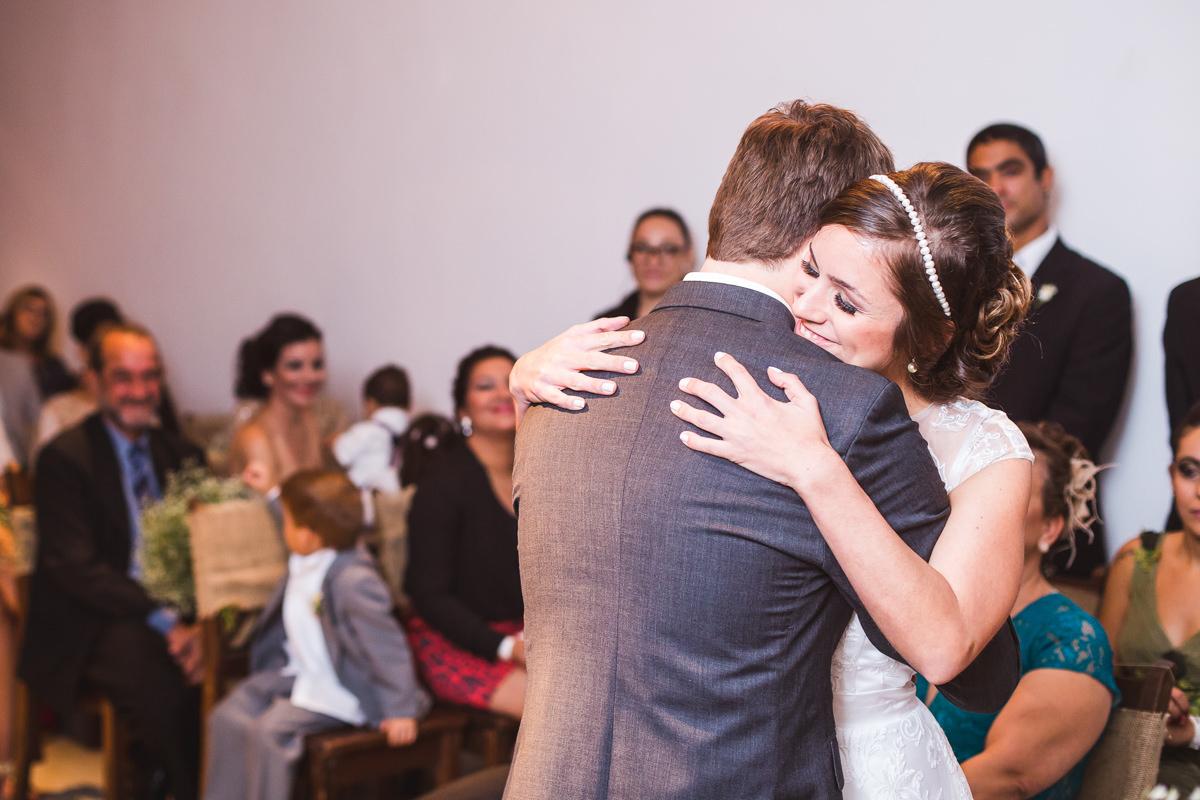 Abraço emocionado dos noivos Karine e Pedro na cerimônia do seu casamento na Galeria Scenarium/Rio Scenarium, Rio de Janeiro/RJ