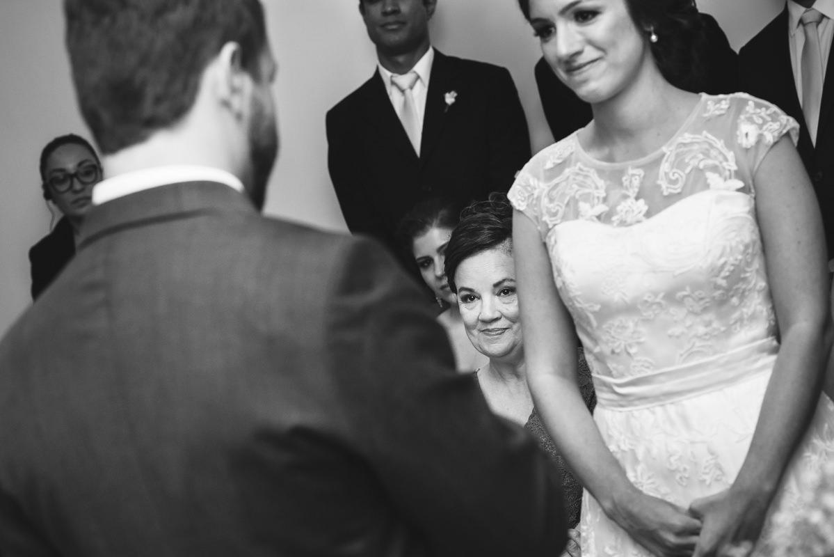 A mãe da noiva observando emocionada os votos do noivo Pedro para sua filha Karine na cerimônia do casamento na Galeria Scenarium/Rio Scenarium, Rio de Janeiro/RJ