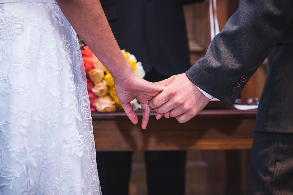Mãos unidas dos noivos Karine e Pedro na celebração do casamento na Galeria Scenarium/Rio Scenarium, Rio de Janeiro/RJ