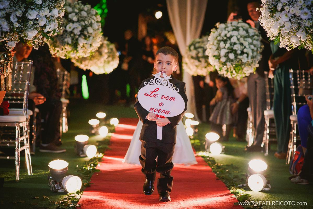 O pajem entrando com a plaquinha na cerimônia do casamento de Priscila e Vitor no Green House Buffet, Ilha do Governador, Rio de Janeiro/RJ