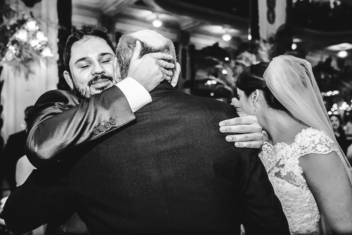 O noivo abraçando o pai da noiva na cerimônia do seu casamento na Confeitaria Colombo, Centro, Rio de Janeiro-RJ