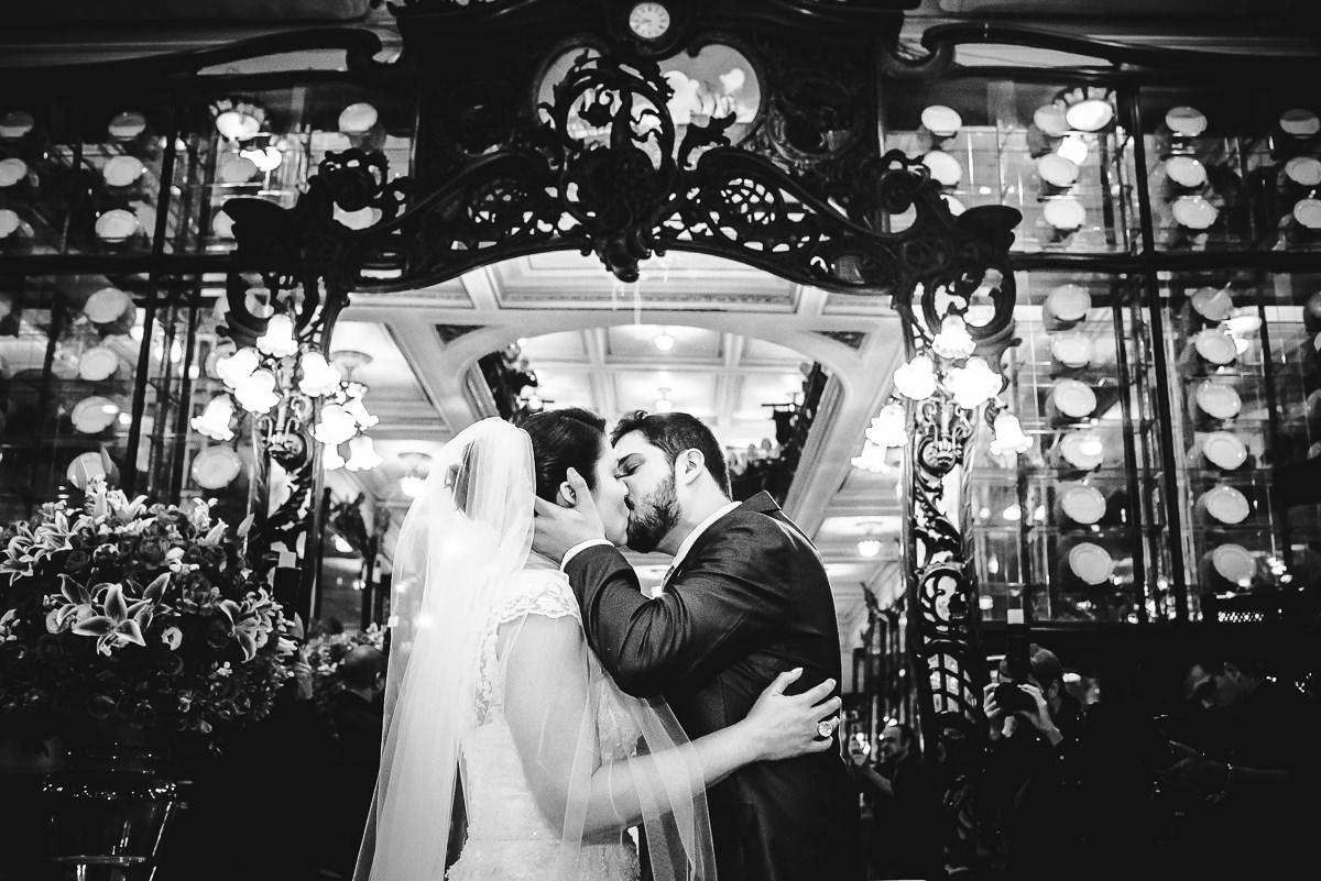Foto preta e branca do beijo no casamento dos noivos Débora e Leonardo Guimarães Joias na Confeitaria Colombo, Centro, Rio de Janeiro-RJ