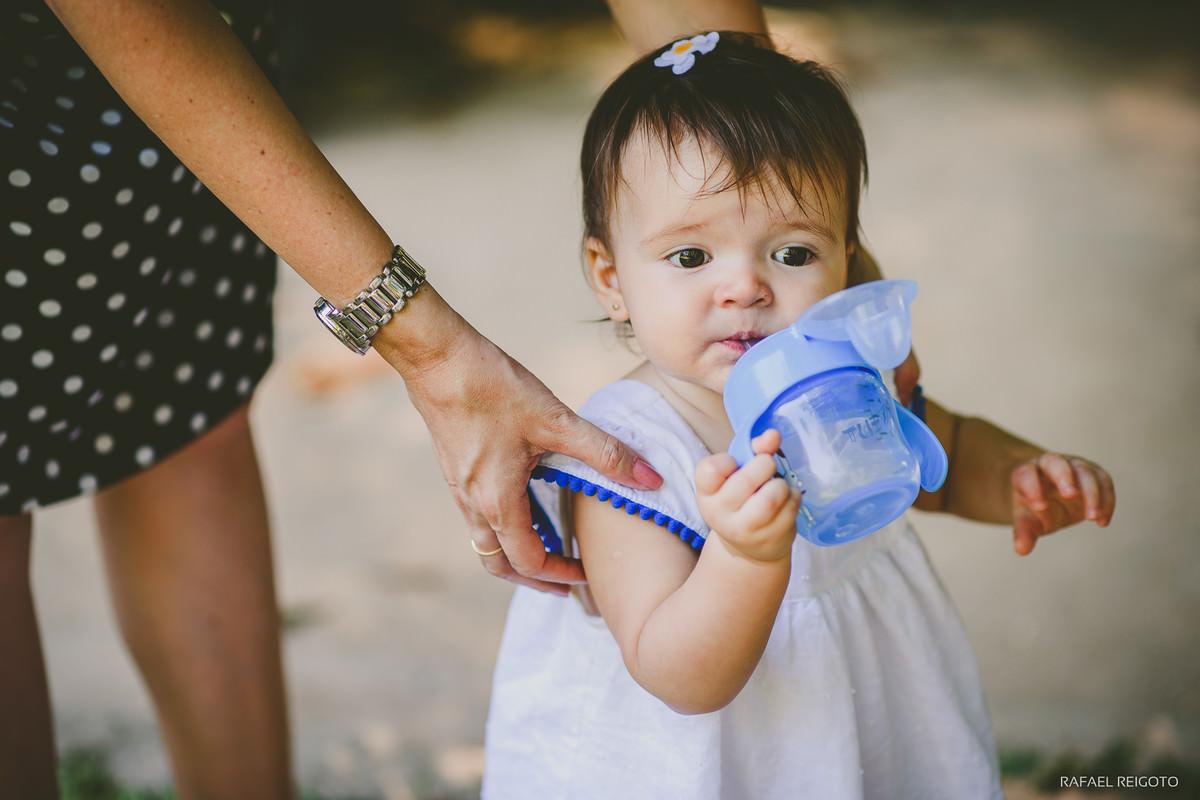 A bebê Catarina se refrescando com sua mamadeira para lá e para cá no ensaio infantil no Parque Lage, Rio de Janeiro-RJ