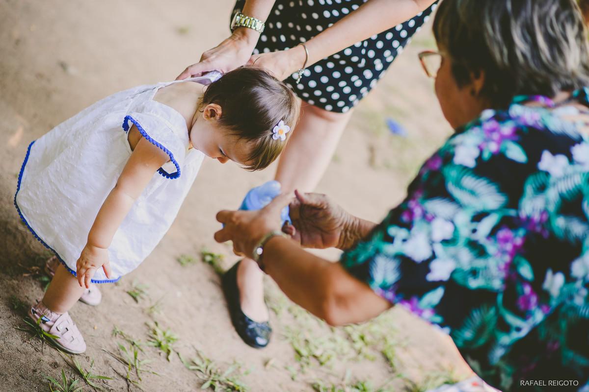 Vovó dando a mamadeira com água para a bebê Catarina se refrescar no dia de calor do ensaio família no Parque Lage, Rio de Janeiro-RJ