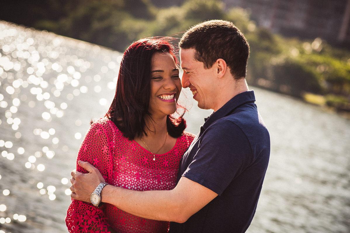 Casal de noivos Priscila e Vitor sorrindo em ensaio na Lagoa Rodrigo de Freitas, Rio de Janeiro.