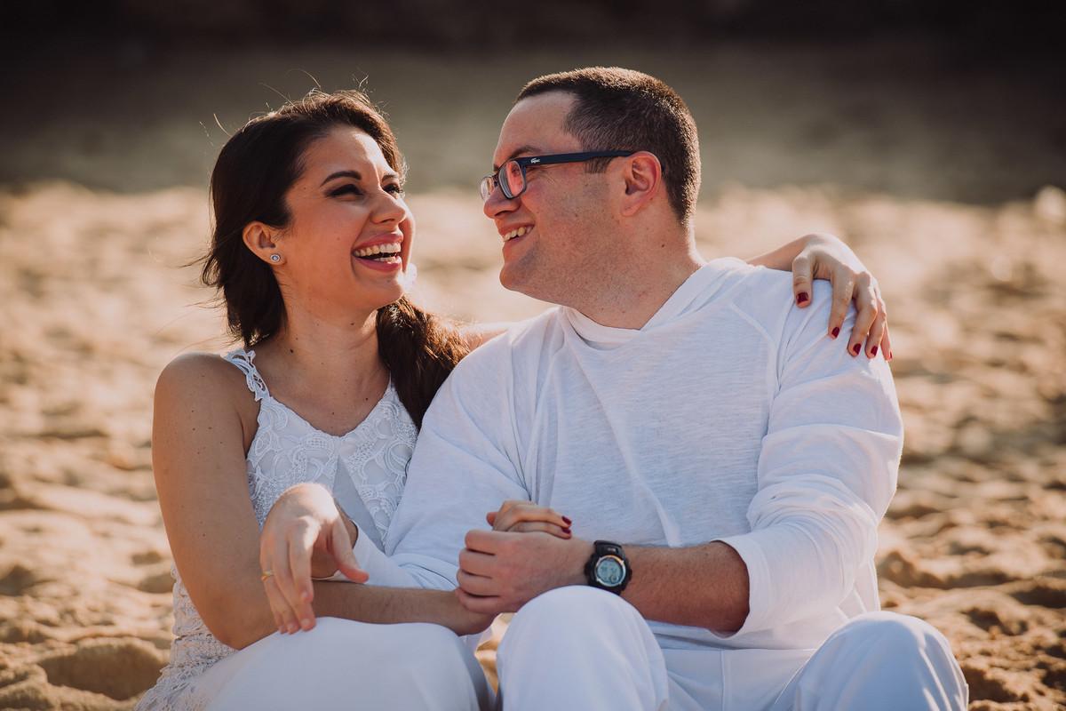 O casal de médicos Bruna e Raphael sorridentes no ensaio pré-casamento na Praia Vermelha, Rio de Janeiro-RJ