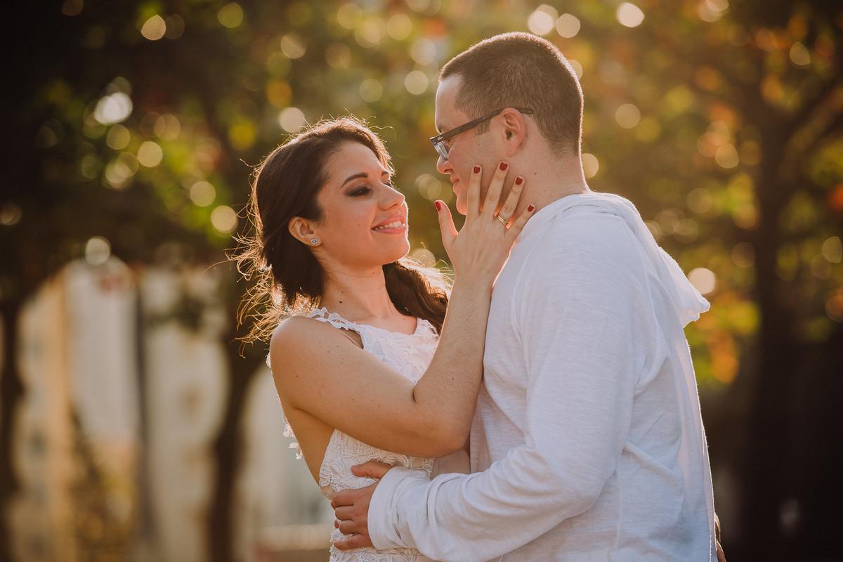 A noiva Bruna fazendo carinho no rosto do seu noivo Raphael no ensaio pré-casamento no bairro da Urca, Rio de Janeiro/RJ