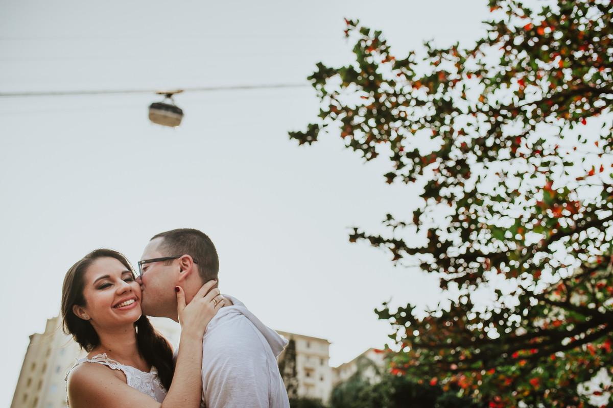 O noivo Raphael dando um beijo em sua noiva Bruna com o bondinho do Pão de Açúcar passando ao fundo, Urca, Rio de Janeiro/RJ