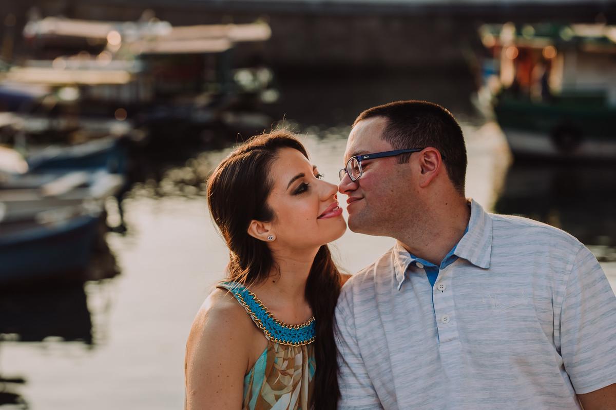 O noivo Raphael chegando para dar um beijo na sua noiva Bruna no ensaio pré-casamento no Quadrado da Urca, Rio de Janeiro/RJ