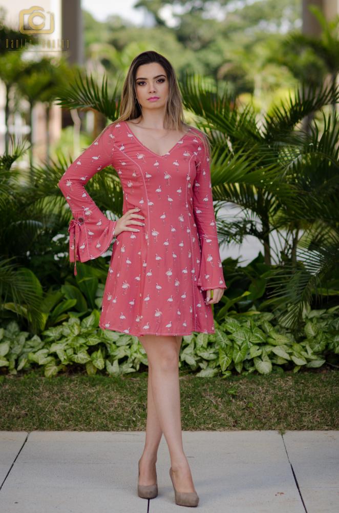 Modelo Glaucia com vestido rosa em pé com mão na cintura