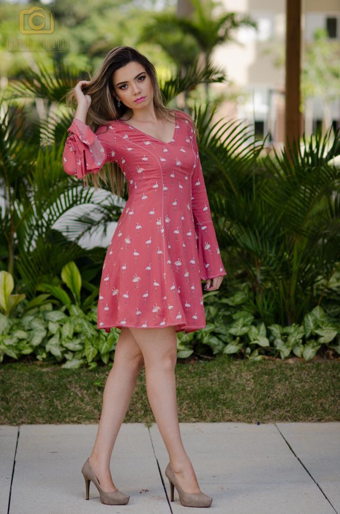 glaucia com vestido rosa em pé e mão no cabelo