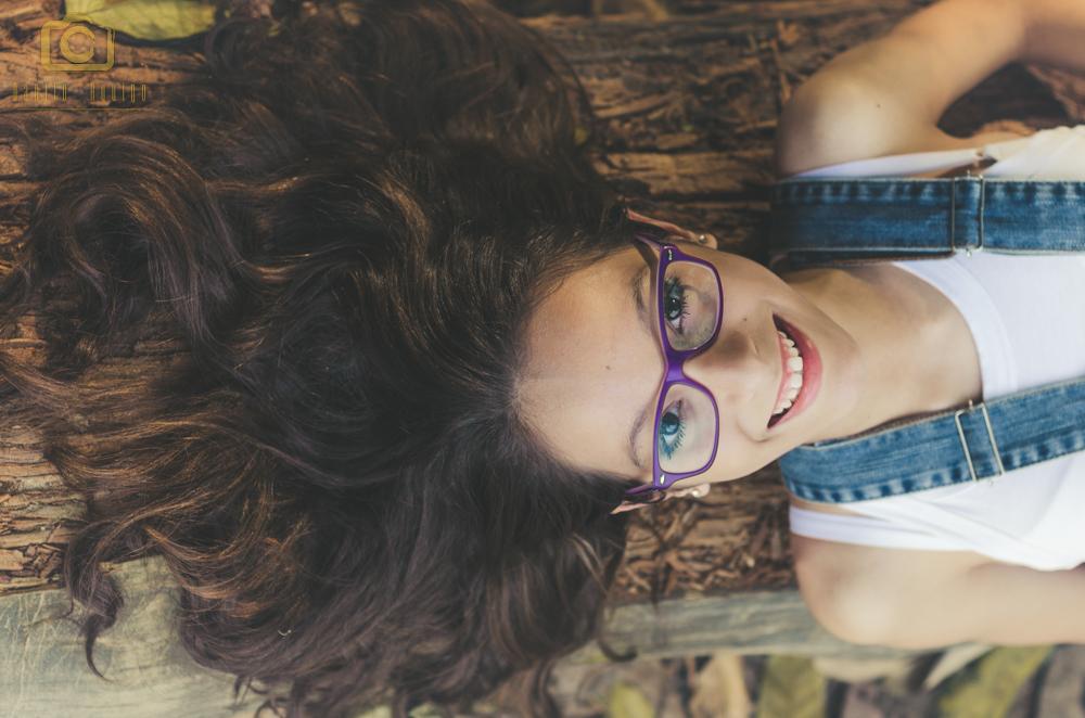 foto tirada de cima com a fernanda deitada no tronco de arvore