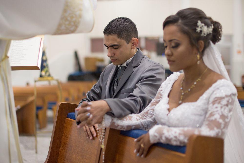 foto do casal de mãos dados ajoelhados no altar