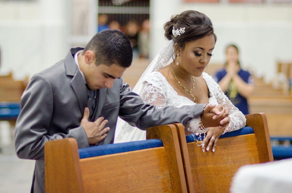 casal ajoelhados no altar rezando