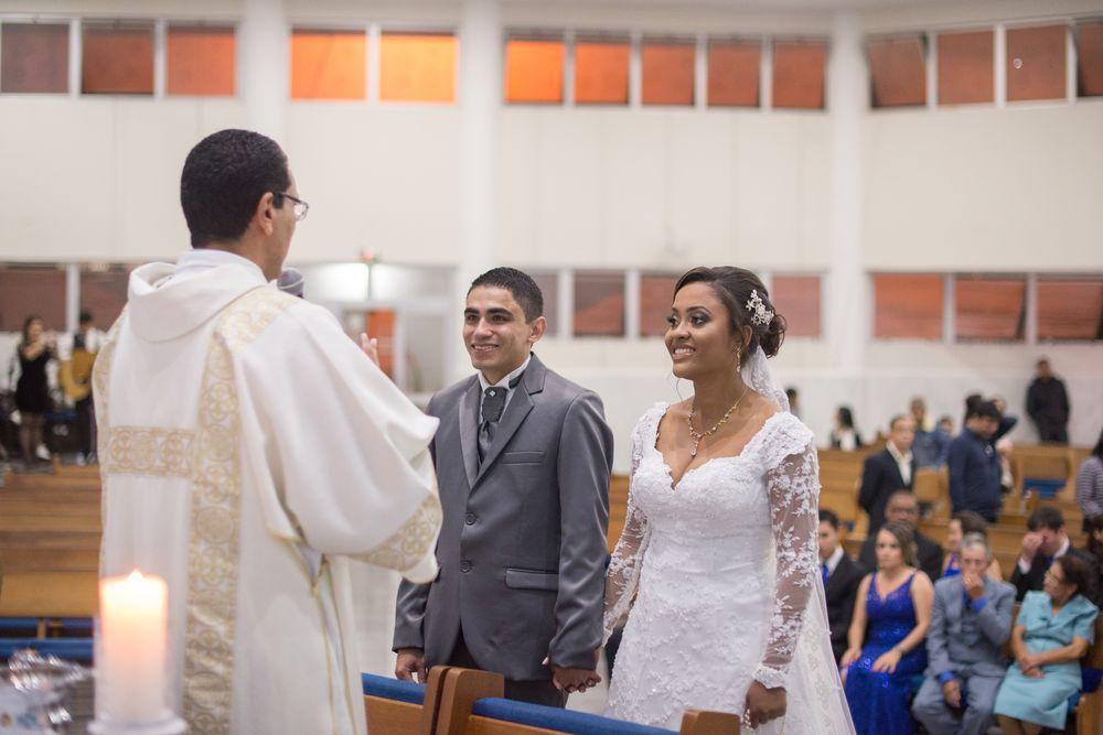 foto do casal sorrindo para o padre
