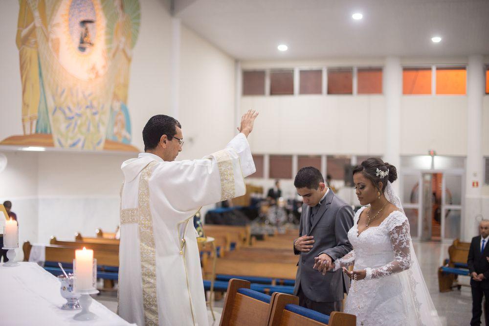 foto do padre com a mão estendida ao casal ajoelhados no altar