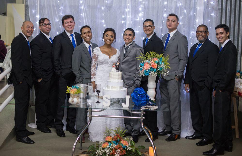 foto com o casal e todos os padrinhos na mesa do bolo