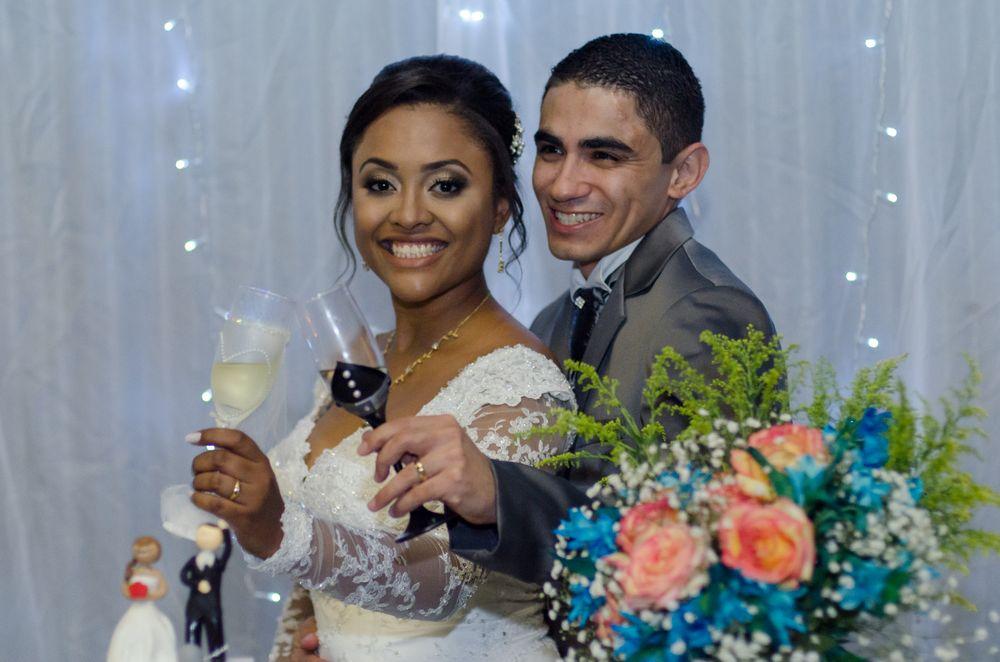 foto da sabrina e joão segurando as taças proximo ao bolo
