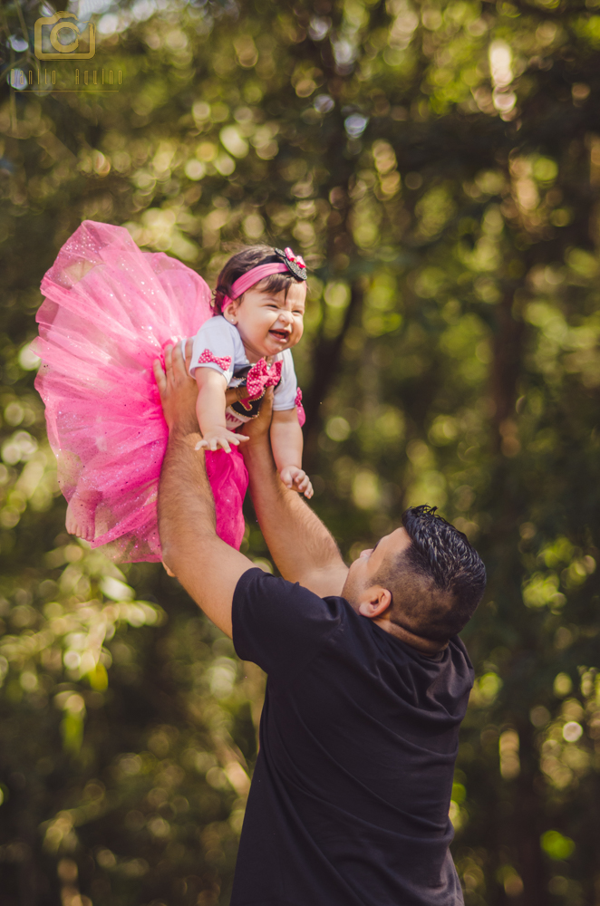 fotografia do pai jogando a laura para cima e ela sorrindo