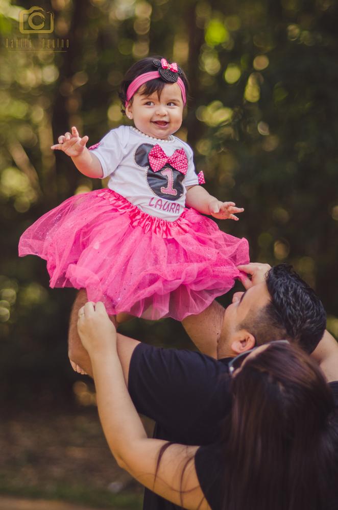fotografia dos pais jogando a laura para cima e ela sorrindo