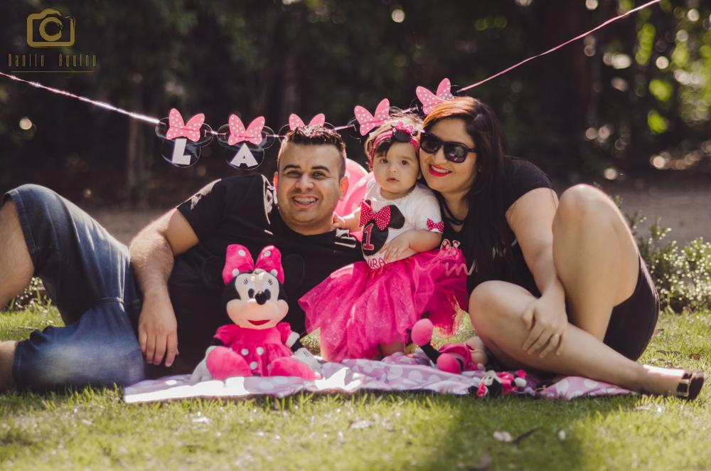 fotografia da laura e os pais sentados olhando para a foto